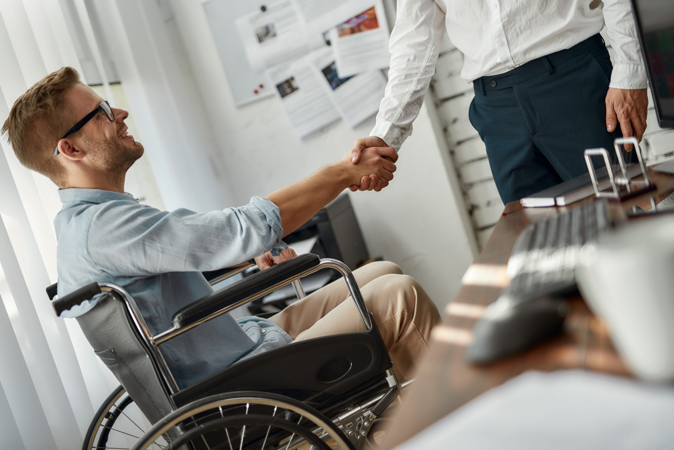 Welcome to our team. Cropped view of young male office worker in a wheelchair shaking hand to his colleague while working together in the creative office. Disability concept
